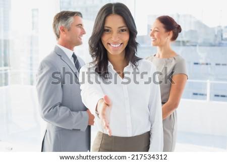 Businesswoman offering a friendly handshake at work - stock photo