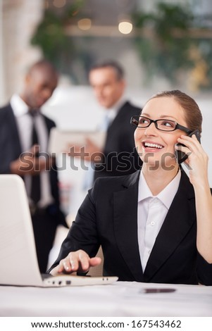Businesswoman on the phone. Cheerful young woman in formalwear sitting at the table and talking on the mobile phone while two colleagues standing on background - stock photo