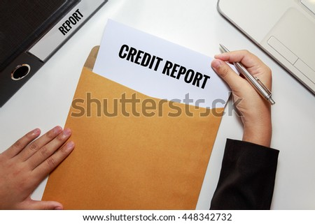 Businesswoman opening Credit report document in letter envelope concept