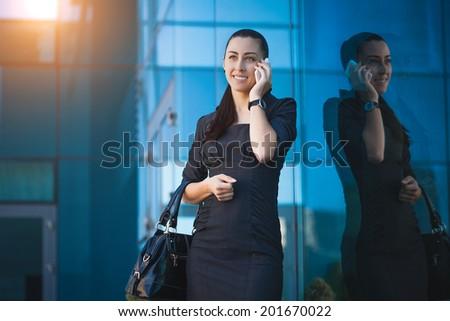 businesswoman or entrepreneur talking on cellphone. City businesswoman working. - stock photo