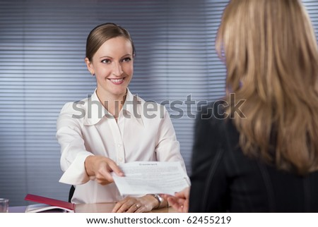 Businesswoman (or notary public) holding pen pointing at signature place on a contract document to woman - stock photo