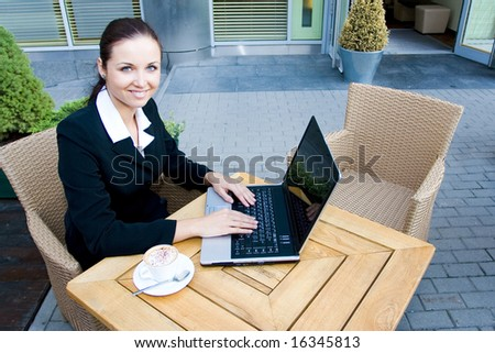 Businesswoman outdoors with laptop - stock photo