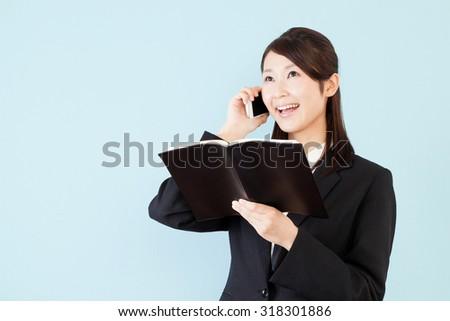 Businesswoman phone pocketbook schedule smile - stock photo