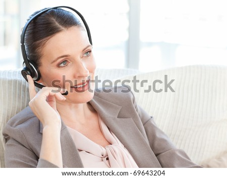 Businesswoman phoning in her living room at home - stock photo