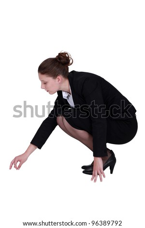 Businesswoman picking a speck up off the floor - stock photo