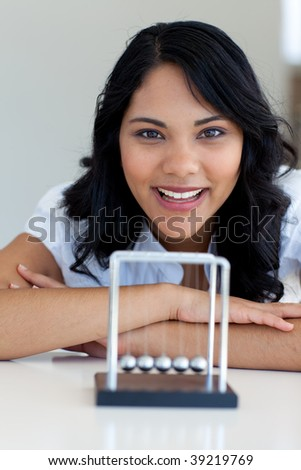 Businesswoman playing with Newton balls in office - stock photo