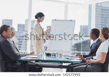 Businesswoman pointing at a growing chart during a meeting in the meeting room - stock photo