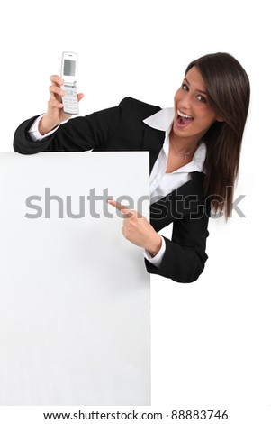 Businesswoman pointing at mobile phone - stock photo
