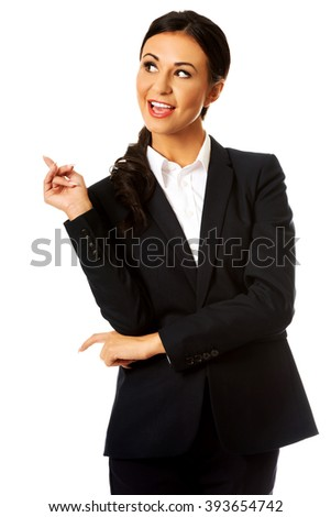 Businesswoman pointing high on copyspace - stock photo