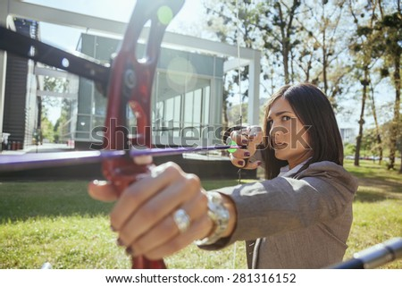 Businesswoman Pointing The Target With Bow And Arrow In Front Of Business Building - stock photo