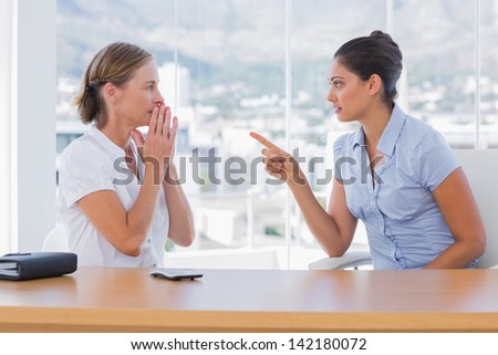 Businesswoman pointing to a colleague in their office - stock photo