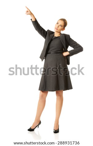 Businesswoman pointing up on space - stock photo