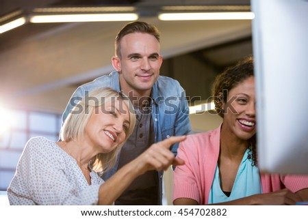 Businesswoman pointing while discussing with colleagues over computer in creative office