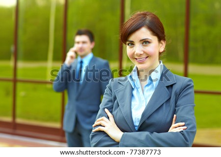 Businesswoman posing in front of business building and businessman in the background talking on the phone - stock photo