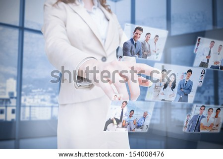 Businesswoman presenting partners pictures on digital interface - stock photo