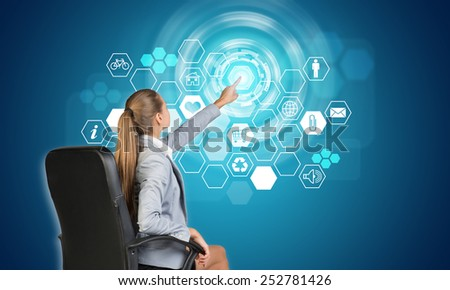 Businesswoman pressing touch screen button on virtual interface with honeycomb shaped icons, on blue background - stock photo