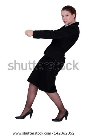 Businesswoman pretending to pull - stock photo