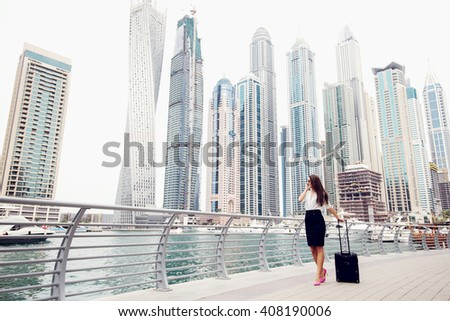 Businesswoman pulling a suitcase in a big city. - stock photo