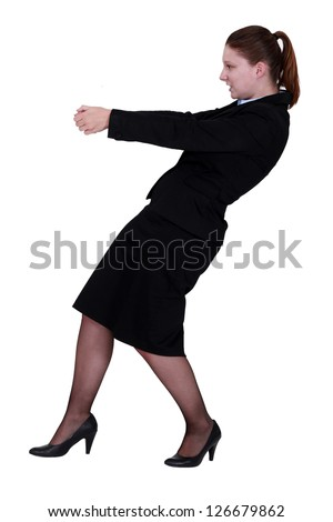 Businesswoman pulling an invisible object - stock photo