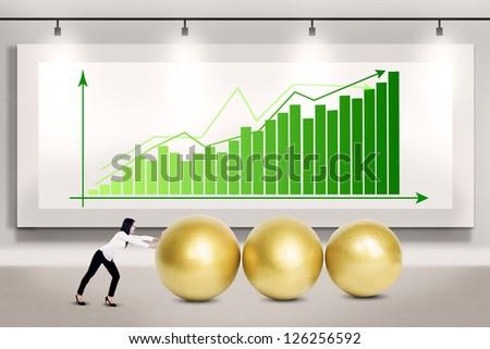 Businesswoman pushing three golden eggs on bar chart background - stock photo