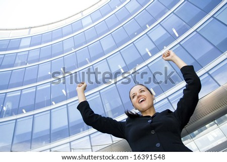 Businesswoman Raising Arms at Skyscraper - stock photo
