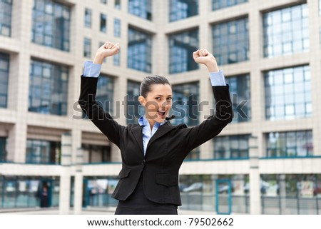 businesswoman raising arms standing front skyscraper - stock photo