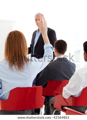 Businesswoman raising her hand up at a conference. Business concept. - stock photo