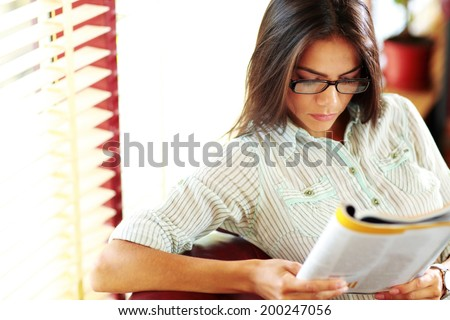 Businesswoman reading magazine in modern office - stock photo