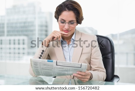 Businesswoman reading newspaper at her desk in bright office