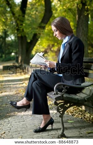 businesswoman reading newspaper on break,  outdoor - stock photo