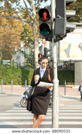 businesswoman reading the newspaper leaning on the traffic light - stock photo