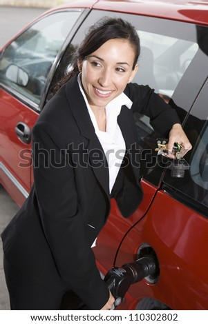 Businesswoman refueling her car - stock photo