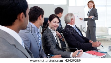 Businesswoman reporting sales figures to her team in the office - stock photo