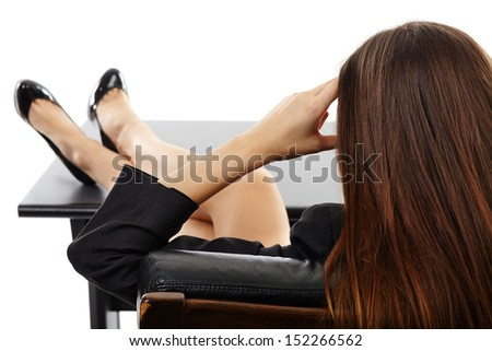 Businesswoman resting her legs on the desk