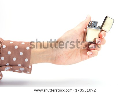 Businesswoman's hand holding cigarette lighter with flame - stock photo
