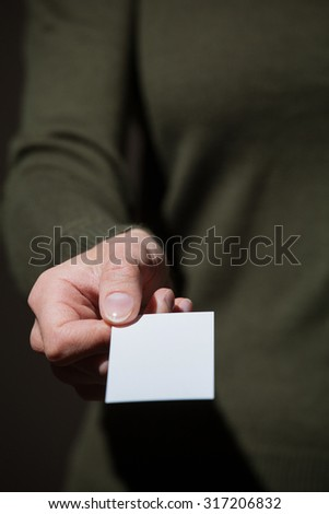 Businesswoman's hand reaching out a business card on dark background