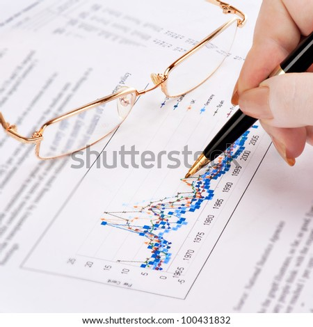 Businesswoman's hand showing diagram on financial report with pen. - stock photo