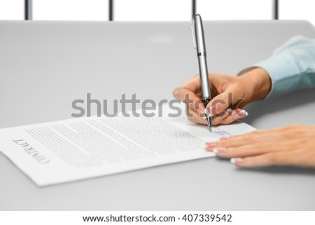 Businesswoman's hand signs a document. Signing paper on white background. One step makes many changes. Think before you move on. - stock photo