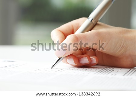 Businesswoman's hand with pen completing personal information on a form