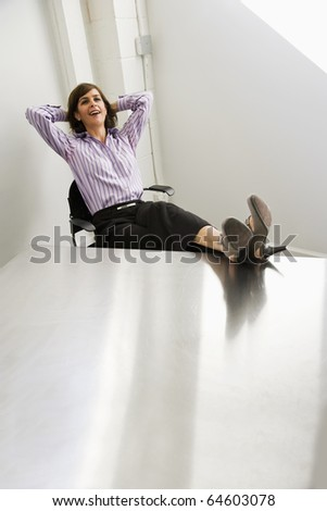 Businesswoman, 40s, smiling and relaxed with feet resting on office table - stock photo