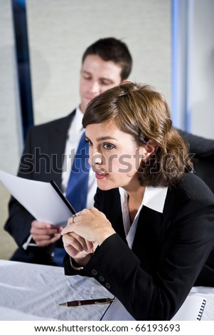 Businesswoman, 40s, watching presentation and with male colleague sitting behind, focus on woman - stock photo