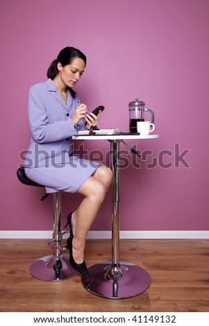 Businesswoman sat at a cafe table writing on her mobile phone during a working lunch. - stock photo