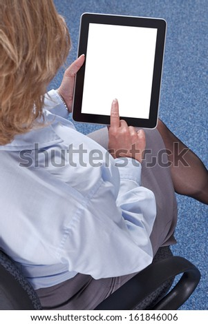 Businesswoman sat in an office using a tablet computer. Clipping path provided for the screen to add your own message or image. - stock photo