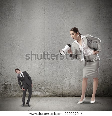 Businesswoman screaming in megaphone on man colleague - stock photo
