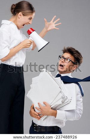 Businesswoman screaming on fearful office assistant - stock photo