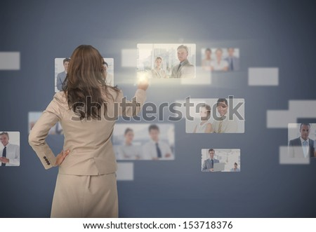 Businesswoman selecting digital interface showing coworkers - stock photo