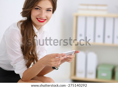 Businesswoman sending message with smartphone in office.