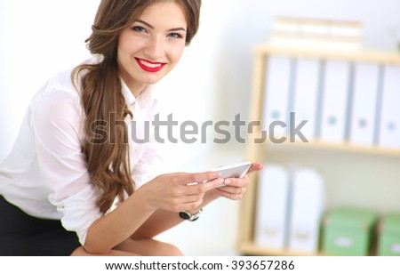 Businesswoman sending message with smartphone in office