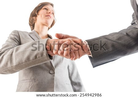 Businesswoman shaking hands with a businessman as they seal a deal or reach an agreement, low angle view. Isolated over white.