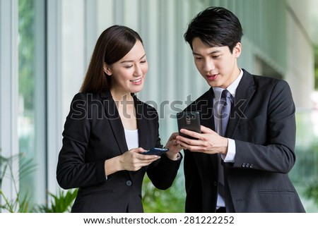 Businesswoman share something on cellphone with her colleague - stock photo